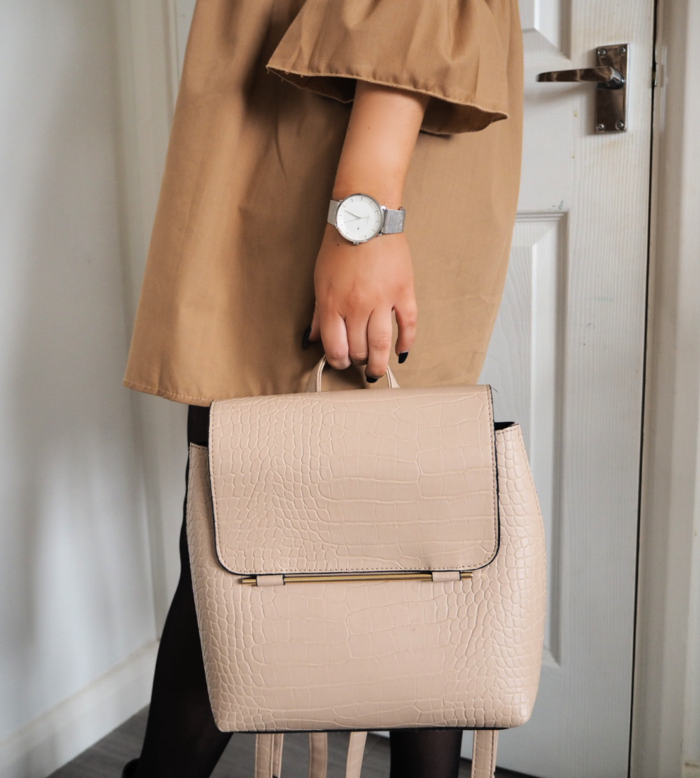 nude backpack and silver watch